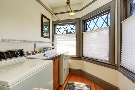 dryer  estate: Old laundry room interior with white appliances and vintage windows with gray trim. Stock Photo