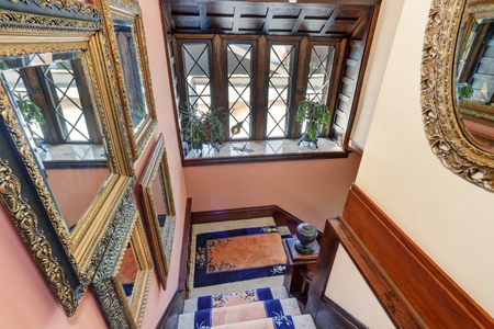 upstairs: Great panoramic view from upstairs. Vintage style house interior. Amazing decorative mirrors in golden frame, staircase with blue rugs and brown trim window.