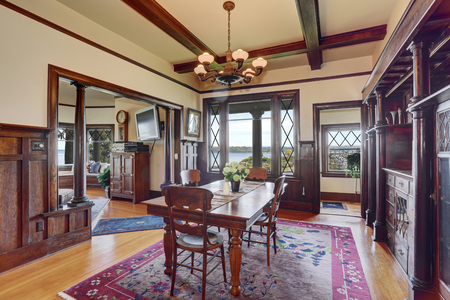 wooden beams: Antique style dining room interior with fresh flowers on the table. Wooden beams ceiling, light tones hardwood floor and brown wood trimmed wall