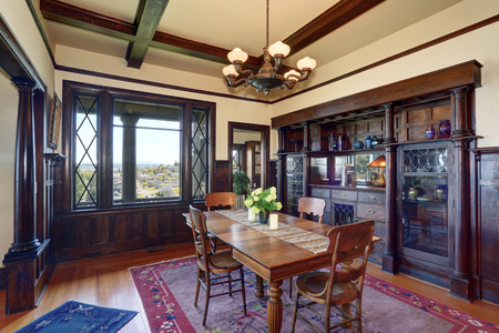 wooden beams: Antique style dining room interior with fresh flowers on the table. vintage buil-in cabinet. Wooden beams ceiling, light tones hardwood floor, and brown wood trimmed wall