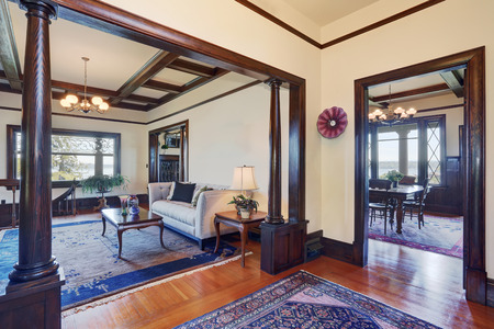 open floor plan: Open floor plan of living room and dining room in old style house. White walls with brown trim and hardwood floor.
