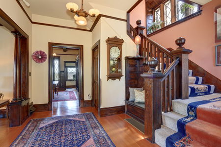 upstairs: Hallway with brown trim and hardwood floor in old house. Wooden staircase with carpet floor and blue rugs. Antique style wall clock. Stock Photo