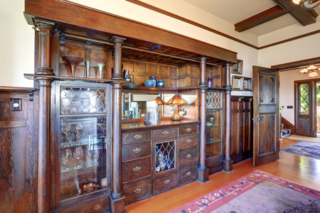 built: Large built in vintage cabinet with columns , glass doors and antique decor.