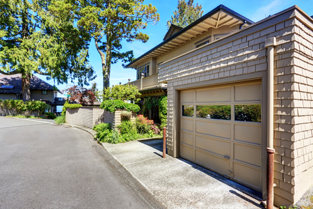 garage on house: Garage space of large craftsman house with beige exterior paint.