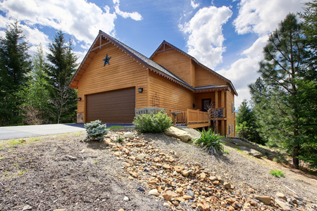 white trim: Traditional wooden Mountain house surrounded by nature. View of garage with driveway