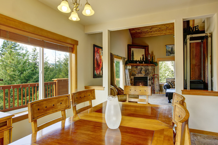 stone fireplace: View of wooden table set in the dining room with marble tile floor. The room is connected with living room and stone trim fireplace in the background Stock Photo