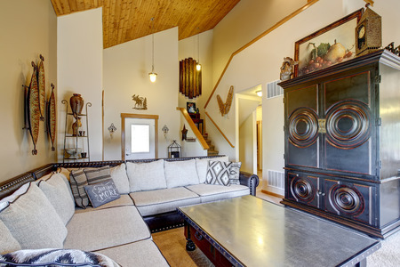 the vaulted: Cozy living room with high wooden vaulted  ceiling and carpet floor. Furnished with large beige sofa, cabinet  and black coffee table with drawers. View of staircase. Stock Photo