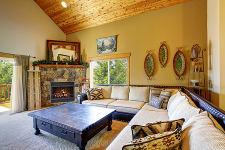 stone fireplace: Cozy living room with high wooden ceiling and carpet floor. Furnished with large beige sofa and black coffee table with drawers. There is also fireplace with natural stone design in the corner.