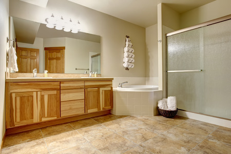 hardwood floor: Elegant bathroom in soft tones with hardwood cabinets and marble tiled floor. White bathtub with tile trim in the corner and glass shower.