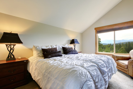 upstairs: Nice upstairs bedroom with vaulted ceiling and carpet floor.White double bed with black pillows and decorative light  lamps beside the bed Stock Photo