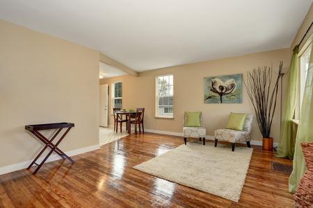 Accogliente salotto beige con pavimento in legno lucido collegato con zona pranzo. Arredata con poltrone d'epoca eleganti e set di mogano tavolo da pranzo.
