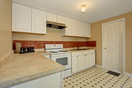kitchen tile: White kitchen room with tile floor and brown back splash tile. House interior.