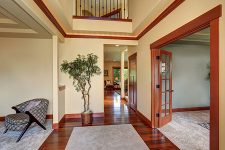 Hallway in creamy colors with polished hardwood floor and brown trim. View of colorful designed armchair and decorative tree in a pot