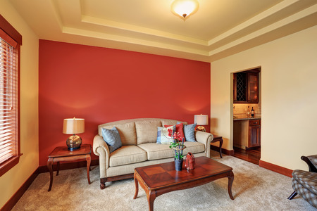 Cozy sitting room with antique beige sofa and red wall behind. Two light lamps with nice decor beside the sofa. View of kitchen room.