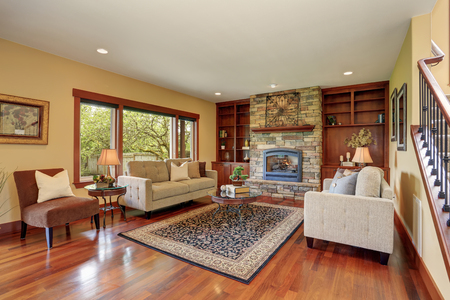 Family room in antique style with natural stone design fireplace , built-in cabinets with open shelves and old sofa set.