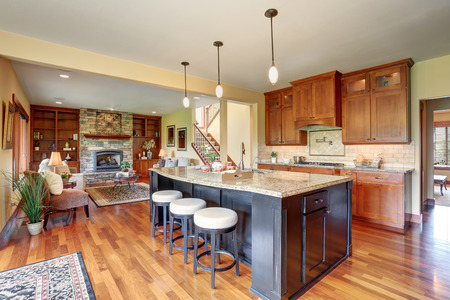 Small kitchen area with open floor plan, view of living room. Kitchen room has black kitchen island with granite counter top and modern stools.