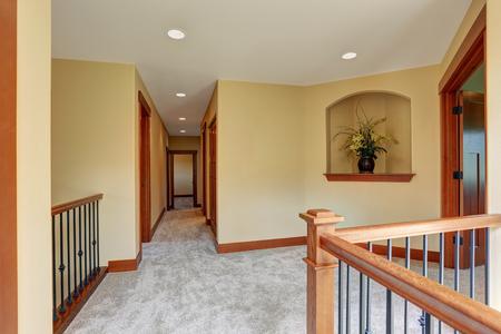 upstairs: Upstairs empty hallway interior with carpet floor. Beautiful fresh flowers in vase create cozy atmosphere. Stock Photo