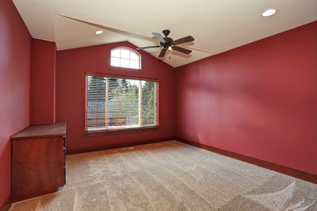 vaulted ceiling: Red empty room with vaulted ceiling and beige carpet