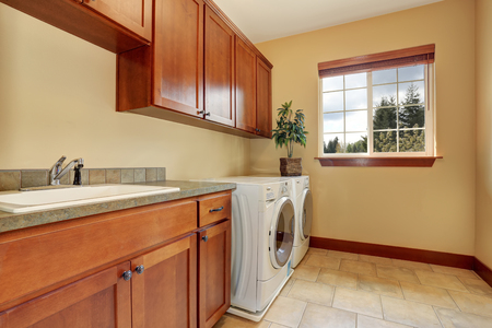 laundry room: Spacious laundry room with white appliances and tile floor. The room Also has cabinets , granite counter top and sink Stock Photo