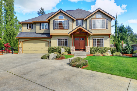 exterior house: Luxurious American home with well kept lawn and green exterior paint.