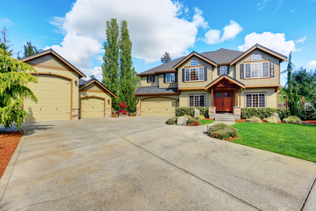 outside house: Luxurious American home with well kept lawn and green exterior paint. Long and wide driveway to double doors garage