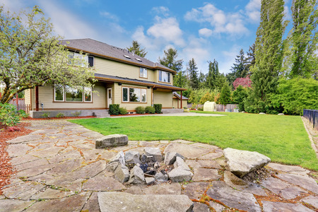 fire pit: Exterior of luxury two story house with grass filled back yard, stone and fire pit