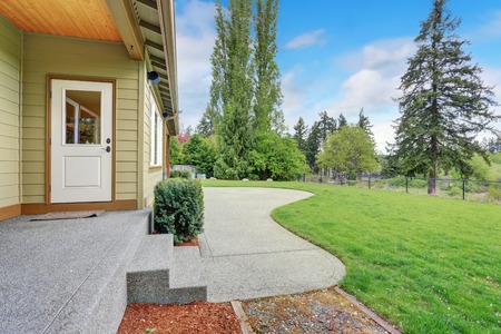 Kleine lege overdekt terras met uitzicht op de achtertuin landschap met betonnen patio Stockfoto