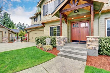 Zicht op huisingang met concrete loopbrug, stenen kolom trim en dubbele deuren. Stockfoto