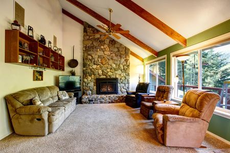 country house style: Great living room interior in American country house. The room has stone trim fireplace and high vaulted  ceiling with wooden beams. Stock Photo
