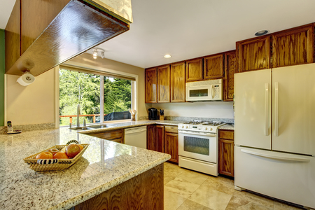 granite: View of kitchen room with hardwood cabinets, granite counter tops, white kitchen appliances and tile flooring