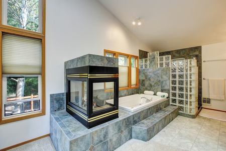 vaulted ceiling: Master bathroom interior with tile flooring and fireplace. Also white bathtub with gray tile wall trim,  large shower and white vaulted ceiling