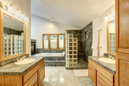 tile flooring: Master bathroom interior with tile flooring and modern cabinets with twin sink. Also large shower with gray tile wall trim and white vaulted ceiling Stock Photo