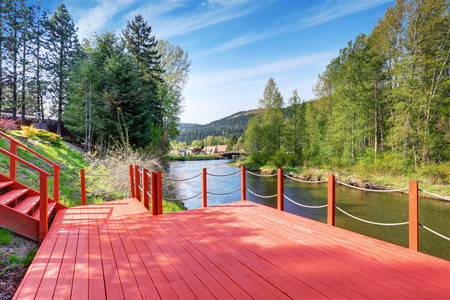 deck: Red walkout deck with staircase on river bank. Backyard view. Stock Photo