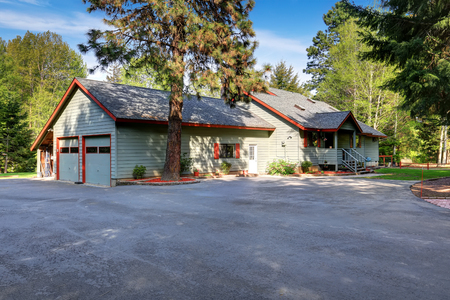 asphalt: American country house exterior with wide asphalt driveway and lots of trees around.