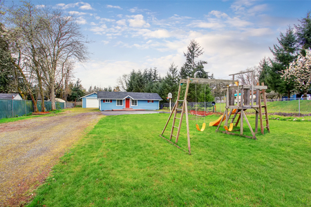 fenced: Fenced backyard with wooden playground for kids. Well kept lawn around