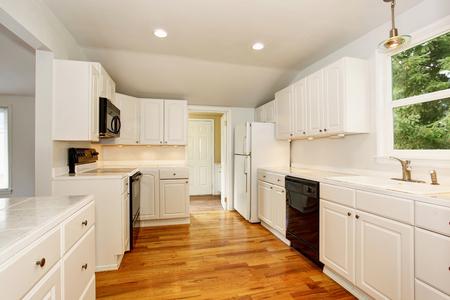 cocina vieja: Blanca vacía sencilla entre la antigua cocina con piso de madera y muebles blancos en la histórica casa de América. Foto de archivo
