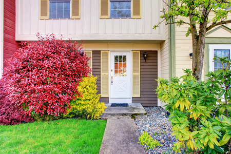 Perfect apartment entrance with white door and nice landscaping desing