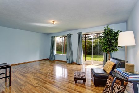 remodeled: Unfinished living room interior with blue walls and blue curtains. Hardwood floor and black leather chair