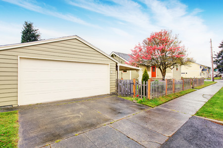 garage on house: Simple house exterior in white color. Separate garage with driveway