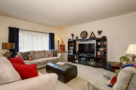 tv set: Cozy living room with beige sofa set and red pillows and black cabinet with open shelves and TV set. Stock Photo