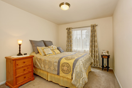 nightstand: Lovely bedroom interior with yellow bedding and pillows, carpet floor and nightstand.