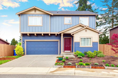 curb appeal: Nice curb appeal of blue house with front garden and garage with driveway Stock Photo