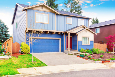 garage on house: Nice curb appeal of blue house with front garden and garage with driveway. House exterior.