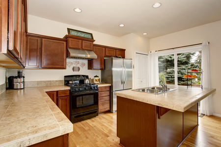 kitchen island: Cozy kitchen room with tile counter top, kitchen island and stainless steel fridge and brown cabinets.