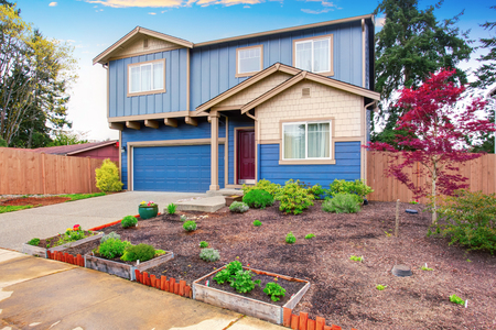 front house: Nice curb appeal of blue house with front garden. House exterior. Stock Photo