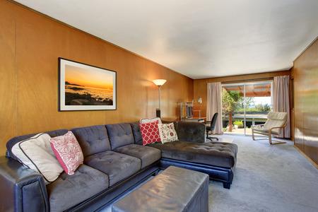 Confortevole salotto con divano scuro grigio set e cuscini colorati. Vista della zona home office.