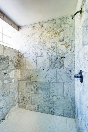 cabine de douche: intérieur de salle de bains. Cabine de douche avec des carreaux de marbre sur les murs et petite fenêtre. Banque d'images