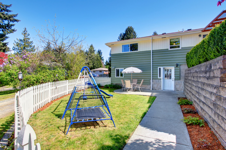 fenced: House exterior. Small fenced back yard with patio area and kids playground