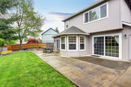 Cozy patio area with concrete floor and table set. Spacious backyard garden with green lawn.