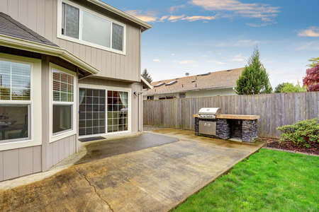 lawn area: Cozy patio area with concrete floor and barbecue. Fenced spacious backyard garden with green lawn.